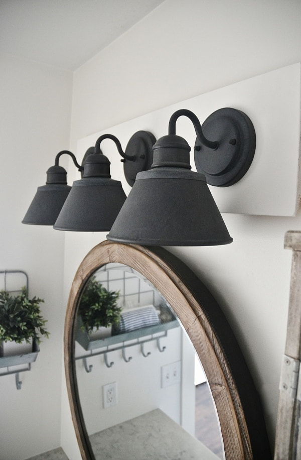 see how to make this super simple farmhouse bathroom vanity light fixture on a budget