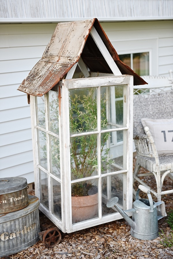 DIY window greenhouse - See how to make this amazing rustic greenhouse. A super easy DIY project that adds rustic charm indoors or outdoors. A great pin for DIY farmhouse decor!