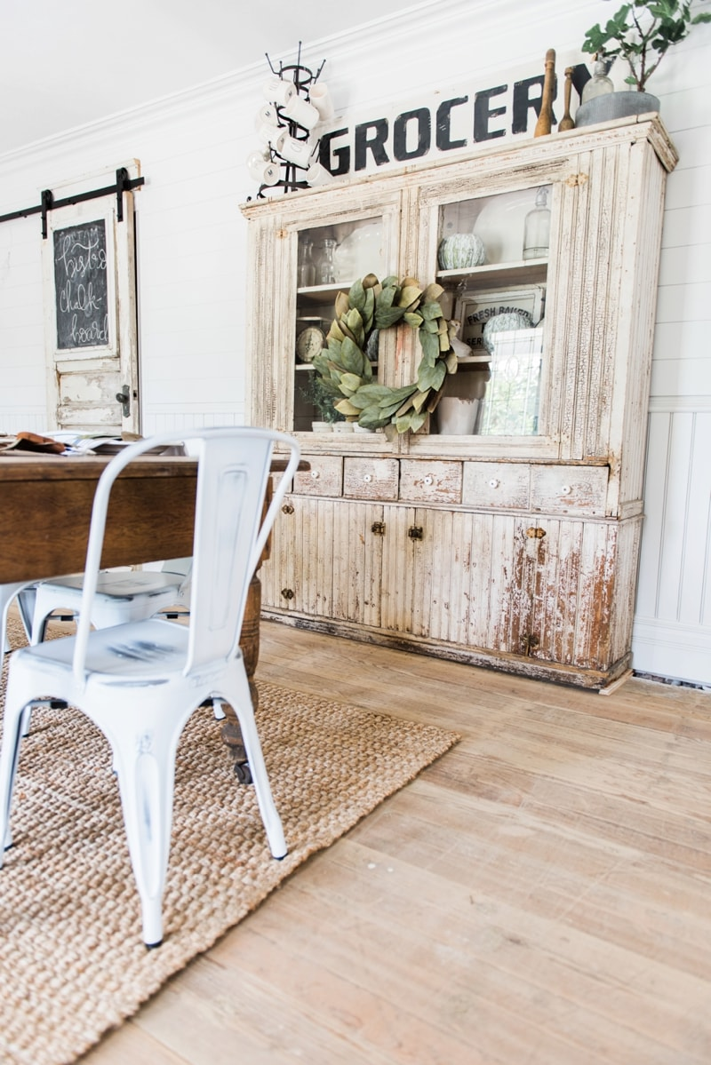 Primitive dining room hutch. Neutral farmhouse dining room. Shiplap walls, primitive furniture, magnolia wreaths, & so much more. Great pin for cottage style/farmhouse style inspiration.