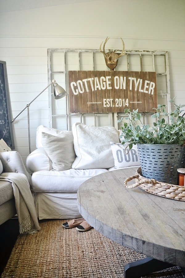 Cozy neutral cottage living room - antique antlers, cozy slipcovered couch, antique windows, & lots of pillows.
