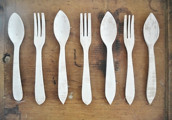 DIY simple & lovely kitchen art! Wooden forks & spoons painted & put on a board. A great way to add charm to your kitchen walls.