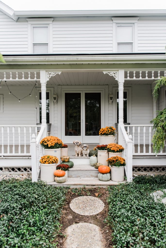 Cozy Rustic Fall porch - Mums in crocks to give a farmhouse porch an instant fall vibe. Great source for farmhouse decor.