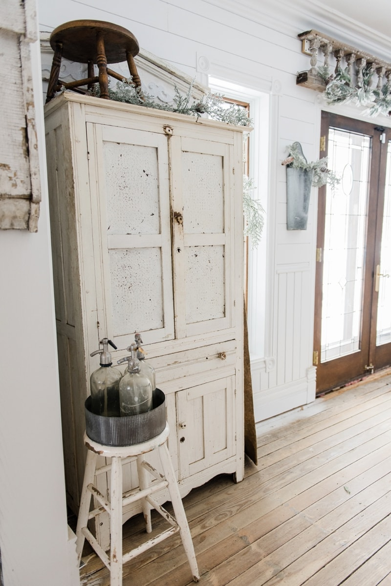 White chippy farmhouse cupboard - Farmhouse winter decor in a farmhouse dining room on LizMarieBlog.Com