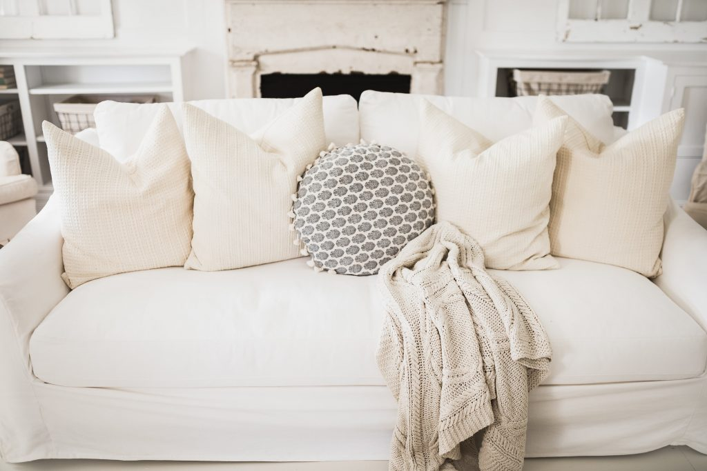 an Ikea sofa with Bemz slipcover on it in a cottage style setting