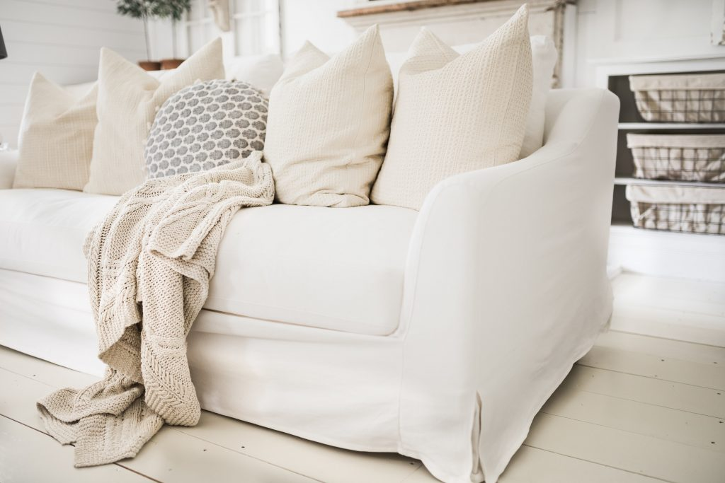 A sofa with white farmhouse slipcovers